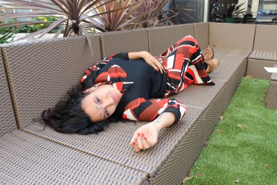Photo of a young woman with long dark hair lying on a outdoor patio furniture in the shape of a couch, one hand is resting on her stomach while the other is lying against the surface of the couch. She has a dress that has an abstract print in black, red-orange and white. The person featured in this image is a self described, 'a black, gross femme, queer punk writer, dancer/actor/model with arthrogryposis'