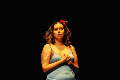 A woman of color with curly brown hair on stage (the background is all black). She has a red flower in her hair. Her hands are clasped together at her chest. She is wearing a light blue tank top.