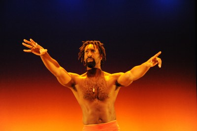 Image of a Black man bare-chested on a stage. His hands are wide open and outstretched. He has a beard and short dreadlocks. The stage is light in orange, black and blue starting from the floor up.