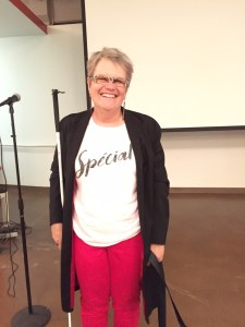 A white woman with short hair is standing with her white cane by her side. She is wearing a long black jacket, red pants and a white shirt that says, 'Special.' She is standing behind a classroom with a white board in the back.