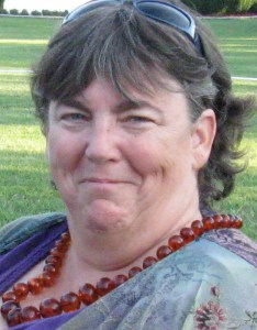 An older white woman with brown hair with bangs on her forehead. She has a pair of sunglasses on her head and is wearing a beaded necklace and a multicolored shirt. In the background is a grassy lawn.