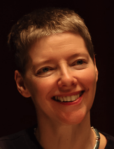 Photo of a white woman with short blonde hair. She is smiling and looking partially sideways from the camera. The background behind her is completely black. She has a black scoop neck shirt and a necklace made of a silver or silver-looking metal.