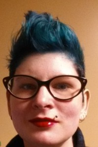 Young white woman with blue hair styled upward like a mohawk (but not). She has cat-eyed eyeglasses on and bright red lipstick.