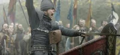 Image description: screenshot from an episode of Vikings, an original series on the History Channel. Ivar the Boneless is a young Viking warrior in full battle gear. He has a helmet over his head and nose. Sitting in a chariot, he is leading his army giving orders and one arm raised.