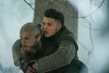 Image description: screenshot from an episode of Vikings, an original series on the History Channel. Ivar the Boneless is a young Viking warrior and he is being carried on the back of his friend and mentor Floki. The outdoor background is a snowy forest.