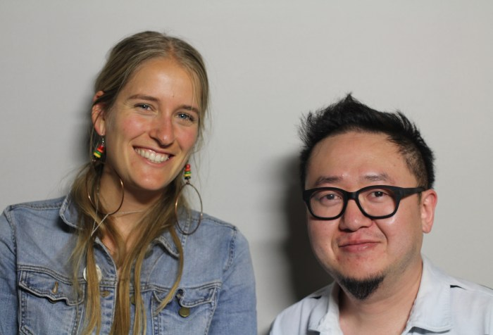 A photo featuring Steve Lee and Ali Murphy, taken on October 2nd, 2014. Ali Murphy is on the left, wearing a blue denim jacket and gold hoop earrings. Ali appears to be white with long blonde hair and blue eyes. She is smiling. Steve Lee is on the right, wearing dark framed glasses and a white collar shirt. He is Asian/American with short dark hair and dark colored eyes.