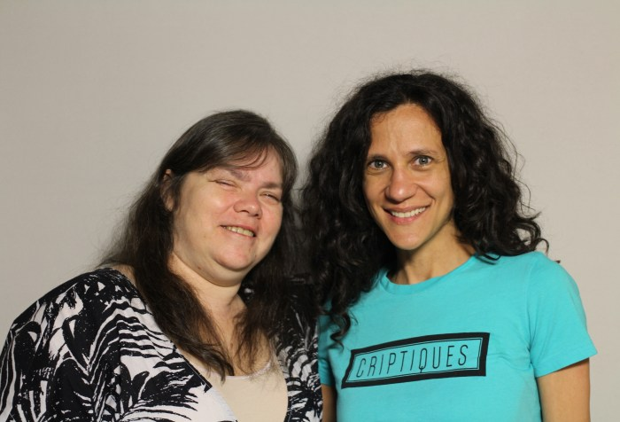 "A photo featuring Lavaun Heaster and Cheryl Green taken on April 22, 2015. The woman on the left is Lavaun Heaster. Her family is Hispanic, Native American and white, and she appears to be white. She is wearing a black and white cardigan with a beige tank top. Her hair is long and brown, and she is smiling at the camera. The woman on the right is Cheryl Green. She appears to be white, has long, wavy, dark brown hair, green eyes and is smiling at the camera. She is wearing a turquoise tee-shirt that says the word ""criptiques"" printed in a black-framed rectangle."