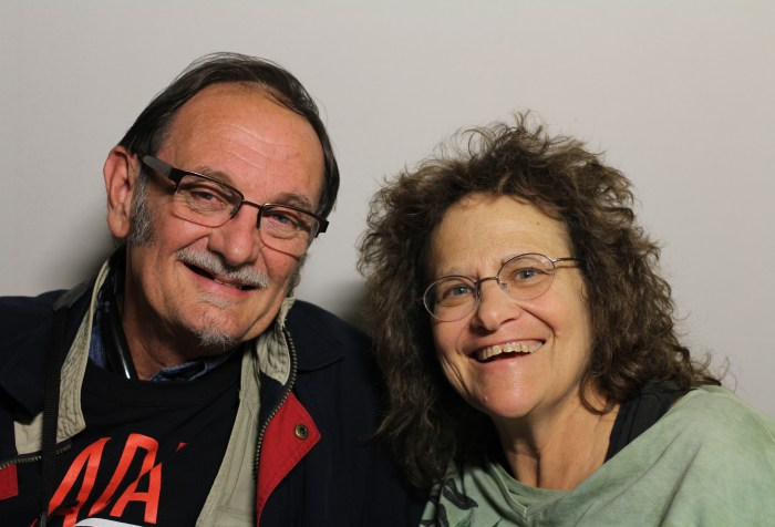 A photo featuring Tom Olin and Marilyn Golden taken on November 19th, 2014. They are both looking at the camera and smiling. The person on the left is Tom Olin. He appears to be white, and is wearing a black jacket and a black t-shirt. He has dark hair combed to the side and is wearing glasses. The person on the right is Marilyn Golden. She appears to be white, and is wearing a light green shirt. She has long brown hair and glasses.