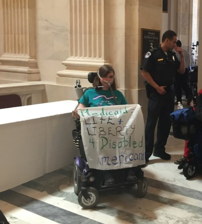 Laura Halvorson in her bipap breathing mask and power wheelchair wearing a turquoise ADAPT Disability Integration Act shirt. Next to her is another ADAPTer and police officers getting ready to exit the Dirksen Senate Building after getting arrested on June 22, 2017 outside Mitch McConnell's office. She is holding a banner that says Medicaid = Life + Liberty 4 Disabled Americans.