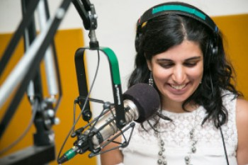 Photo of a South Asian American woman in front of a microphone at a radio station. She is wearing headphones and has long black hair. She is smiling and her eyes are downcast looking at something. She is wearing a white sleeveless shirt and a silver necklace. Photo credit: Ann Oleinik