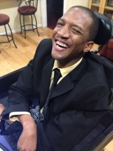 Photo description: Lateef McLeod is smiling and winking, at the camera in his black suit. He is sitting in his power wheelchair and his tray and headrest are visible. To the side of them stools, a hardware floors, and an open doorway. Behind him is a tan bookshelf and a maroon couch.