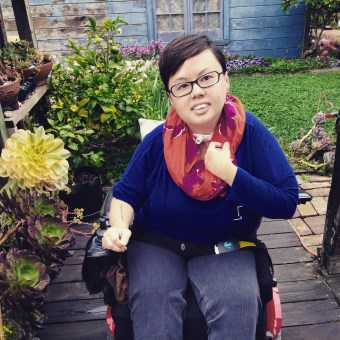 Image description: photo of Stacey in her garden. She has short hair, is mixed race Asian American, and uses a power wheelchair. She is wearing a bright orange scarf and is surrounded by succulents.