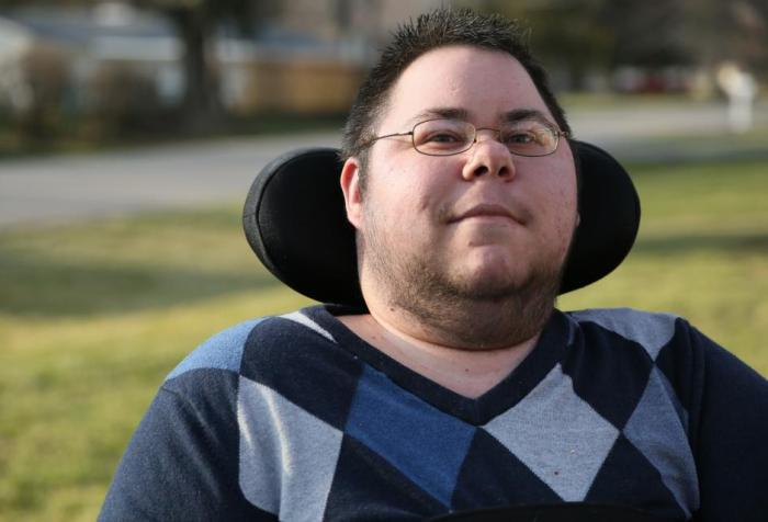 Dominick Evans, a nonbinary trans masculine person looks at the camera, with a slight smile on his face. His eyes are also smiling. He has short, dark spiky hair, and wears glasses. He has stubble along his jaw, cheeks, and chin. He is wearing a argyle sweater with various shades of blue, gray, and black. His wheelchair headrest is visible behind his head, and there is green grass and the neighborhood behind him, faded in the background.