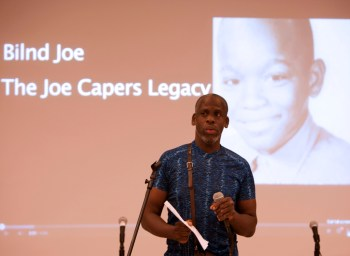 """Image description: Leroy F. Moore, Jr., a Black disabled man giving a lecture. He is standing in front of a microphone and wearing a short-sleeve blue shirt. Behind him on a screen is a slide showing a black and white photo of a young Black child. Left of that photo is text that reads, """"Blind Joe, The Joe Capers Legacy."""""""