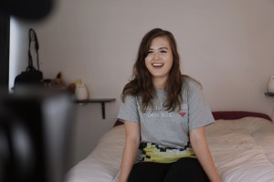 Image Description: Rikki in the middle of filming. She is sitting on a bed in a bedroom, talking/smiling at the camera. Photo credit: createitkind.org