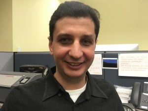 Photo of Walei Sabry smiling, wearing a black collared shirt, inside an office cubicle.