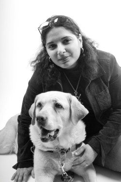 Image description: Black and white photo of an Arab-American woman with dark hair in jeans and casual wear, and yellow Labrador guide dog. Photo credit: Rachel Ellis