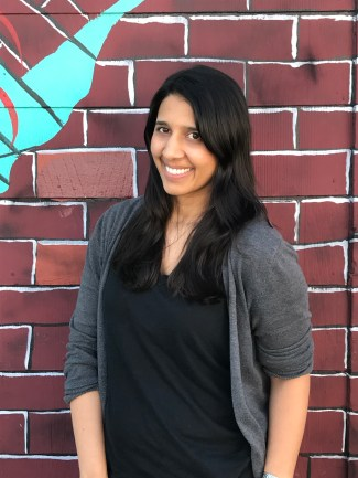 Image description: smiling Indian woman wearing jeans, a black shirt, and grey cardigan standing in front of a painted brick wall.