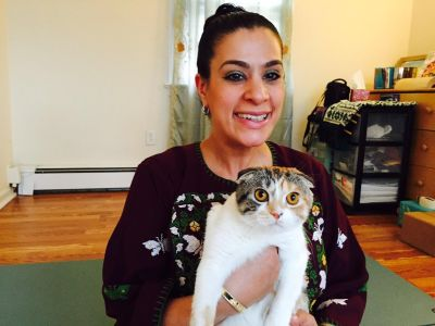 Image Description: Maysoon is smiling. She's wearing green eyeshadow and her dark hair is in a bun. She is wearing a purple dress with white cross-stitched butterflies and is carrying a Scottish fold calico cat named Beyoncé.