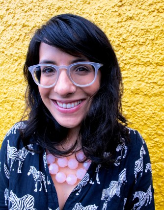 Photo of Neera Jain, a smiling Indian-American woman with wavy shoulder-length brown hair and bangs, clear plastic-framed glasses, and a silver nose ring standing in front of a bright yellow stucco wall. She wears a black shirt-dress printed with white zebras, and a chunky pale pink beaded necklace.