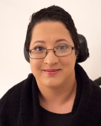 A headshot-style photo of Alejandra Ospina, a Latin American woman with short, dark hair and brown eyes. She is wearing a black top and an open black sweater. She is smiling slightly with her mouth closed, and she is wearing black-framed glasses.