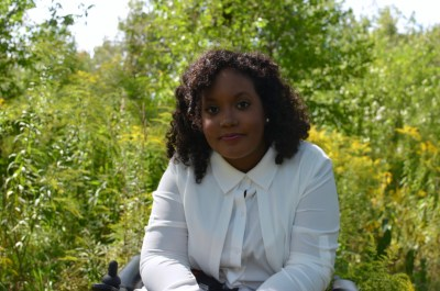 Image description: Black woman in a wheelchair sitting in front of trees looking directly into the camera with a smile.