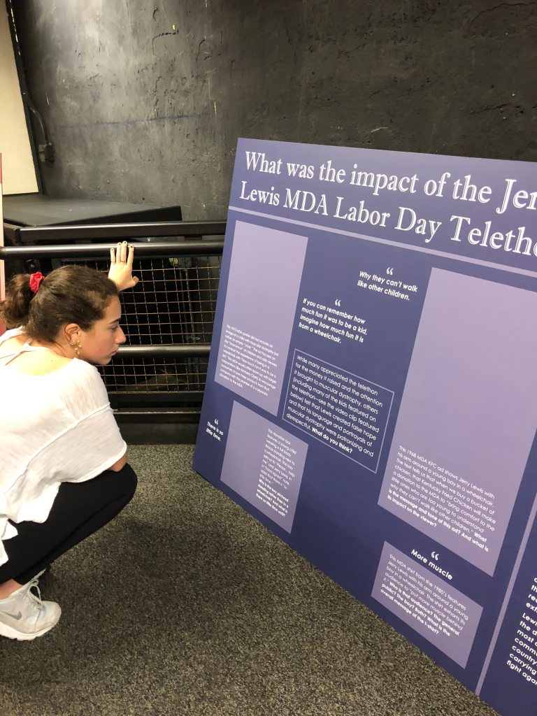 "Student Skylar Kostinden proofreads a large wall panel for a museum exhibit with the title, ""What was the impact of the Jerry Lewis MDA Labor Day Telethon?"" Photo courtesy of Gann Academy. Photo credit: Maya Wainhaus"