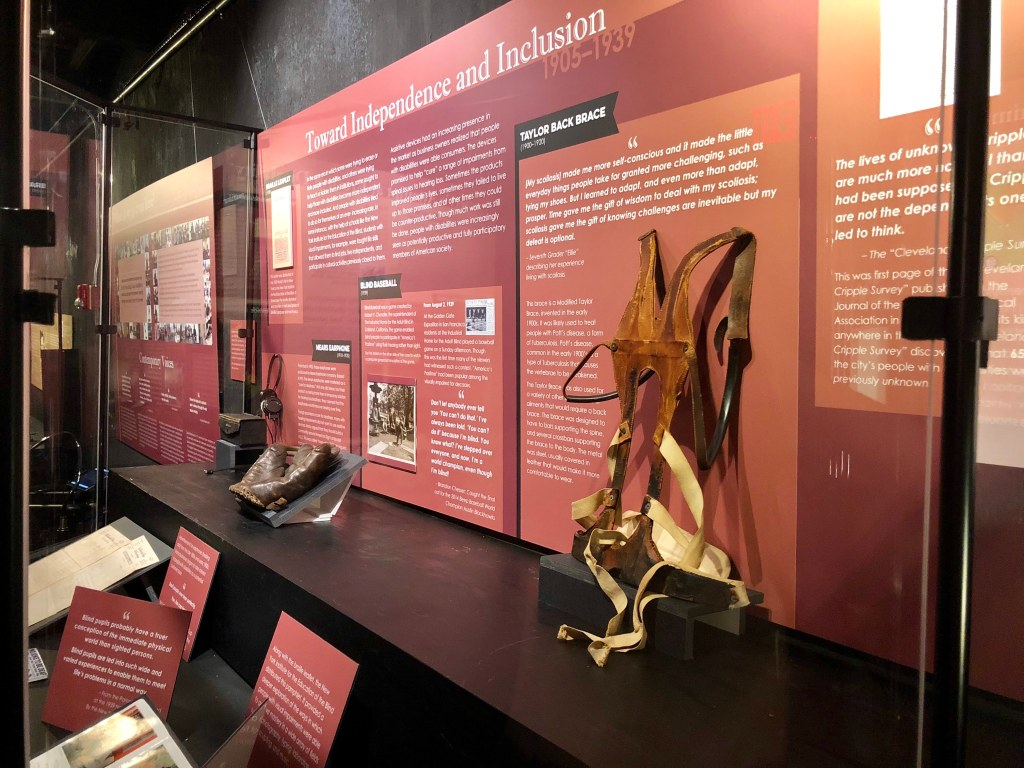 """Disability history exhibit featuring a back brace, a baseball glove, and an early hearing aid. The title for this section: """"Towards Inclusion and Independence 1905-1939."""" Photo courtesy of Gann Academy. Photo credit: Maya Wainhaus"""