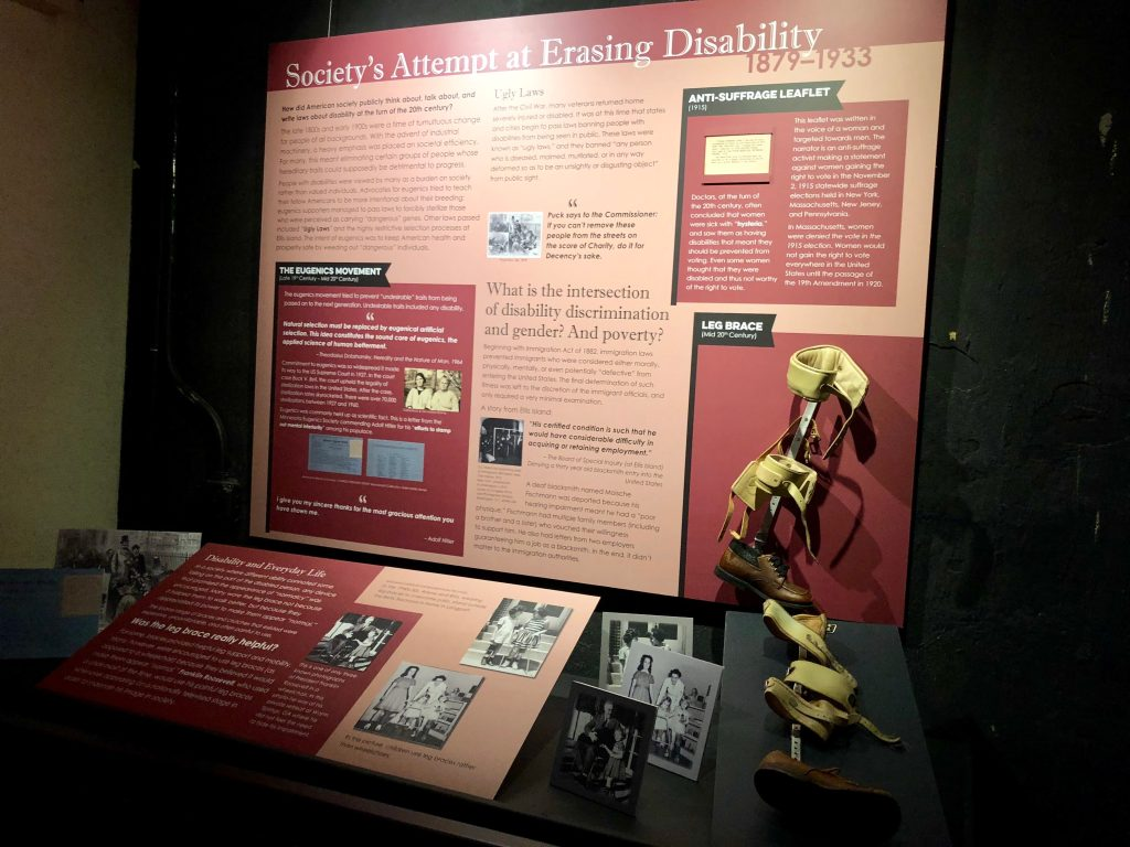 """Museum exhibit on disability showing a leg brace and photos with the with the title """"Society's Attempt at Erasing Disability."""" Photo courtesy of Gann Academy. Photo credit: Maya Wainhaus"""