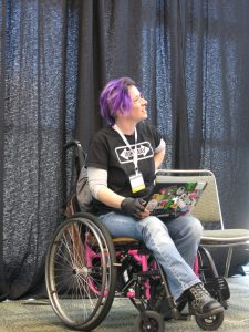 """Image description: A woman wearing jeans and a black """"Wiki Way"""" t-shirt, with purple hair, in a pink manual wheelchair with a sticker covered laptop in her lap."""