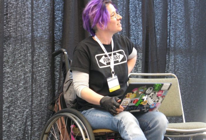"Image description: A woman wearing jeans and a black ""Wiki Way"" t-shirt, with purple hair, in a pink manual wheelchair with a sticker covered laptop in her lap."