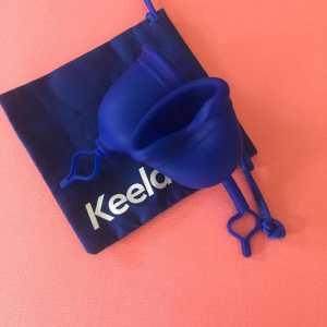 Against a peach colored background, photo of a blue square bag with the word 'Keela' and 2 blue silicone menstrual cups lying on top of the bag.