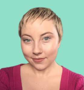 Photo of a woman with pale skin and and a short blonde pixie cut wearing a pink sweater with a teal background.