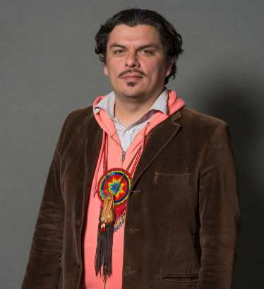 Jean-Luc stands dressed in a button-down shirt, hoodie, and blazer. Hanging from Jean-Luc's neck are a small leather medicine bag and a beaded rosette medallion. Both ornaments are gifts to Jean-Luc from grandmothers in the Mexica tradition.