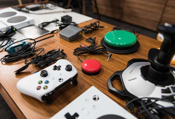 Photo courtesy of Microsoft. A table with the Xbox Adaptive Controller and an array of accessories such as a joystick, microswitch, foot pedal and other items.