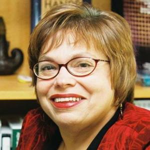 Judy Heumann with short brown hair and red glasses looks directly at the camera smiling, wearing a red blouse.