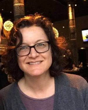 Photo of Claudia Center, a white woman with wavy shoulder-length brown hair. She is wearing glasses and a heather gray cardigan with a purple t-shirt underneath. She is smiling at the camera.