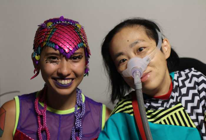 On the left is Sky Cubacub, a non-binary queer and disabled Filipinx human wearing colorful chainmaille headpiece in magenta, purple, turquoise and yellow. She is wearing a sleeveless purple mesh tank and a necklace that looks like chains in purple and magenta. On the right is Alice Wong, an Asian American disabled woman in a wheelchair. She is wearing a top with a geometric print with stripes, in aqua, black, white, and red. She is wearing a mask over her nose attached to a tube for her ventilator.