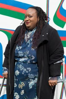 Imani stands on her crutches in a blue dress and jacket in front of a blue red and green mural wall. Photo credit: Madasyn Andrews