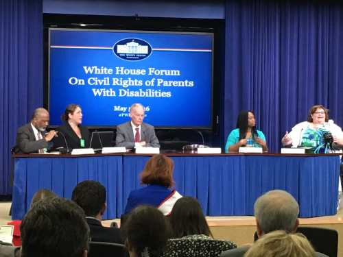 """Five individuals sitting behind a draped table in front of a screen that reads """"White House Forum on Civil Rights of Parents with Disabilities"""". At the end of the table is a brunette haired woman sitting in a wheelchair and speaking passionately. Photo courtesy of Rebecca Cokley."""