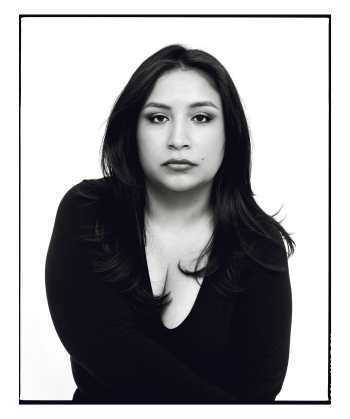 Black and white photo of a Latina facing the camera with a serious face, her hair down, and wearing a black v-neck top.