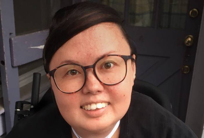 A mixed race Korean and white queer person smiles head on at the camera. She has big glasses and is wearing a crewneck. Her trach and wheelchair can be seen.