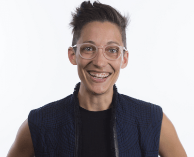 Photo of Liz Jackson, a queer white disabled person with short hair. She is wearing eyeglasses, a navy vest with a black t-shirt underneath. She is smiling broadly. Photo credit: Ryan Lash