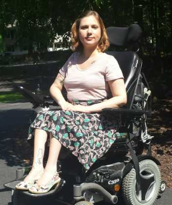 A young, white woman with short blonde hair is pictured outside. She is wearing a pink tee-shirt, black skirt with pink and green design, and matching heels. She is smiling toward the camera and seated in a black power wheelchair.