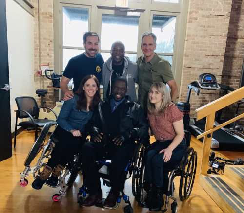 Group photo of 6 people from a shoot on NCIS: New Orleans. In the front row from left to right are three wheelchair users composed of two white women and one Black man: Katherine Beattie, Daryl Chill Mitchell, and Teal Sherer. In the back are three white men standing left to right: Kurt Yeager, LeVar Burton, and Scott Bakula. Photo courtesy of Katherine Beattie.