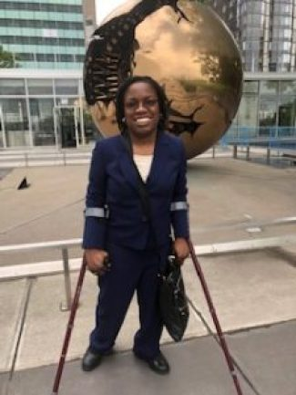 A Black woman in a blue suit standing on crutches in front of a golden replica of the globe outside of the United Nations headquarters in New York.