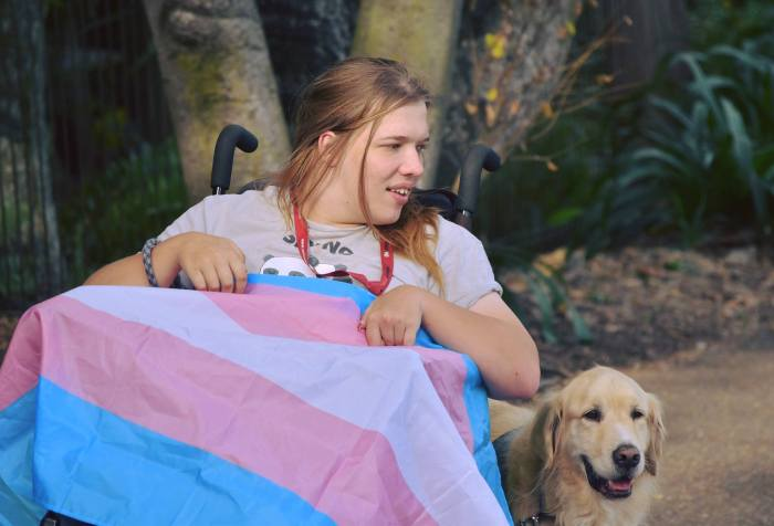 Photo of Annabelle Oxley, a young white woman draped in a trans flag and her assistance dog Jasper, a golden retriever.