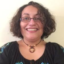 Light brown Puerto Rican woman in her 30s wearing a black top. She is wearing glasses and a brown circular necklace. She is smiling and has curly shoulder-length hair. She is wearing glasses and a brown circular necklace.