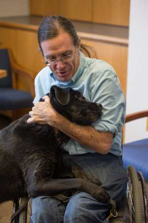 Bill Peace, a white man wearing glasses and long hair pulled back in a pony tail. He is wearing a light denim shirt looking down with affection at a black labrador dog nuzzling at his lap. He is in a manual wheelchair.