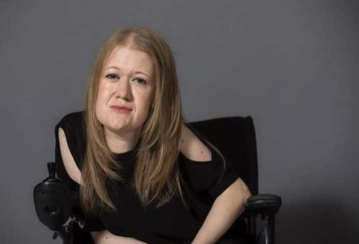 Picture is of Frances sitting in her wheelchair; smiling, wearing a black top and her blonde hair down.